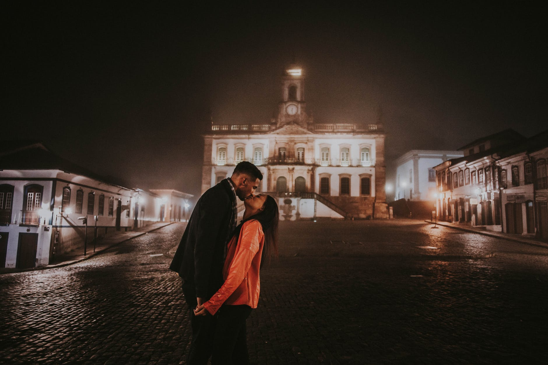 photo of couple kissing at night with building in the background
